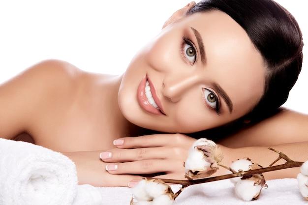 後ろに固定された茶色の髪、きれいな新鮮な肌、大きな目と白い壁に花とタオルでポーズをとっている裸の肩を持つ魅力的な女の子、クローズアップ。