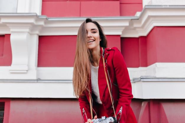 Attraente ragazza con capelli castani in posa in città con la macchina fotografica