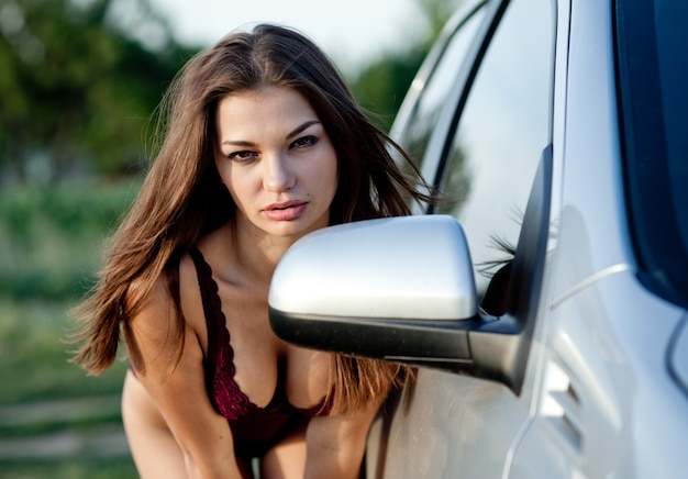 Attractive girl with brown hair, in purple underwear posing standing by white car. photo outdoors with blurred background