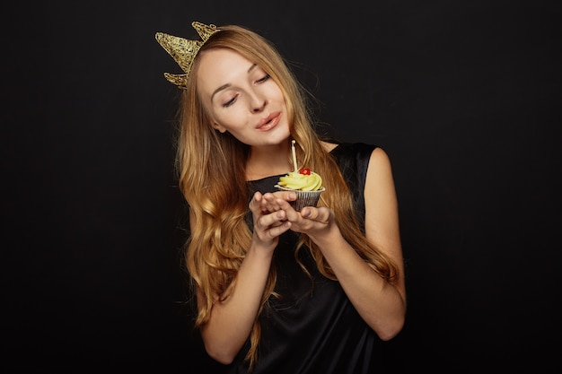 Attractive girl with a crown and cupcake