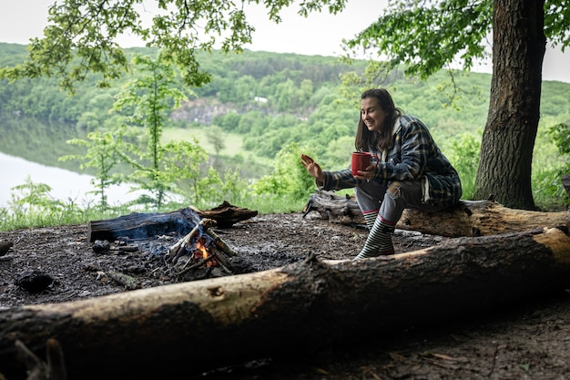 Una ragazza attraente con una tazza in mano si siede su un tronco e si scalda vicino a un fuoco nella foresta.