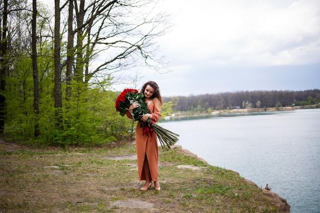 Привлекательная девушка с вьющимися волосами и улыбкой на лице с огромным букетом красных роз на фоне голубого озера. теплый летний день, счастливая молодая женщина, эмоции радости