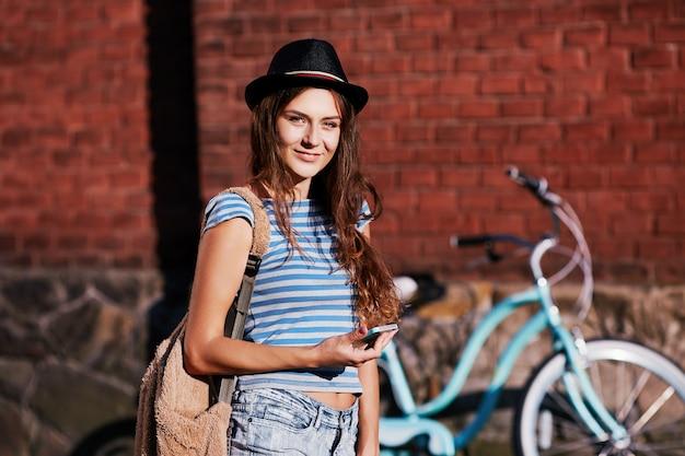 모자, 위쪽 및 자전거와 서 휴대 전화, 여름 사진을 들고 반바지를 입고 곱슬 머리를 가진 매력적인 소녀.