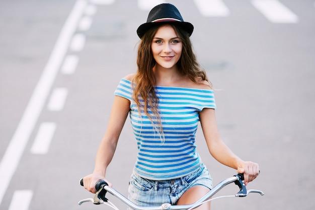 모자, 위쪽 및 공원, 여행, 초상화, 여름 사진에서 자전거와 함께 서 반바지를 입고 곱슬 머리를 가진 매력적인 소녀.