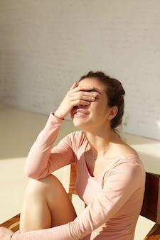 かわいい笑顔の魅力的な女の子は、明るい太陽の下で目を細めて手で顔を覆い、自宅のモダンなインテリアでポーズを楽しんでいます。家で残りを楽しんでいる笑顔の若いファッションモデル、コピースペースの壁