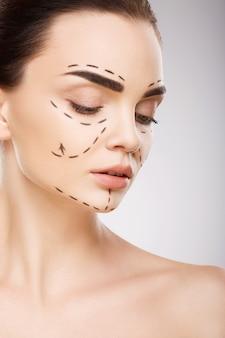 Привлекательная девушка с темными бровями на фоне студии с линиями перфорации на лице, концепция пластической хирургии, крупным планом портрет.