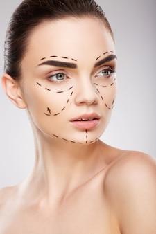 Привлекательная девушка с темными бровями на стене с линиями перфорации на лице, концепция пластической хирургии, крупным планом портрет.