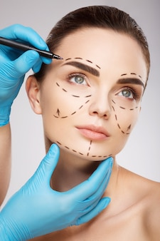 Attractive girl with dark eyebrows at studio background, doctor's hands wearing blue gloves drawing perforation lines on face, plastic surgery concept.