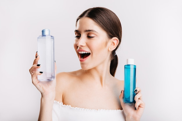Attractive girl with dark hair poses on white wall and chooses what kind of micellar water to use.