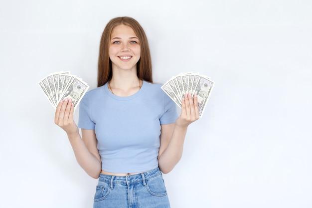 灰色の背景にドルで魅力的な女の子。ビジネスと金融