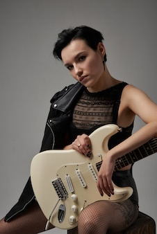 Attractive girl with an electric guitar in a leather jacket and in red glasses in the studio on a white background