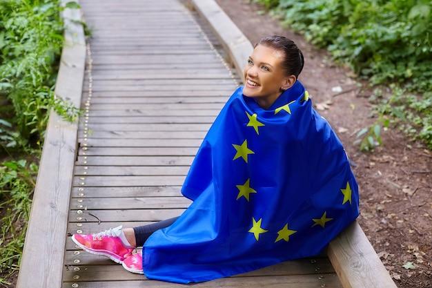 森林公園でポーズをとるeu旗を持つ魅力的な女の子