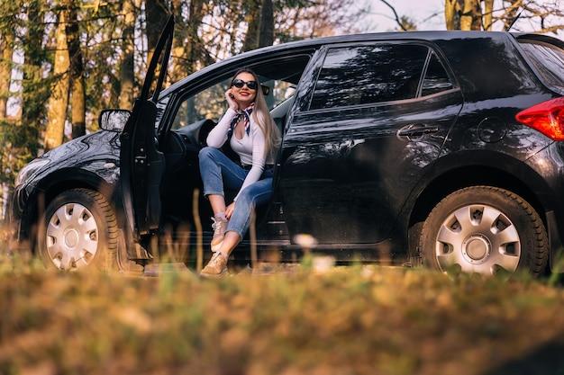 Привлекательная девушка в очках, сидя в открытой черной машине