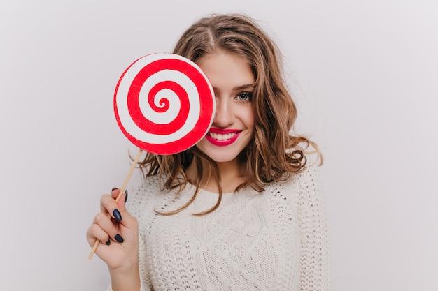 회색 눈과 밝은 입술을 가진 매력적인 소녀는 롤리팝으로 얼굴의 일부를 덮고 웃고 있습니다.