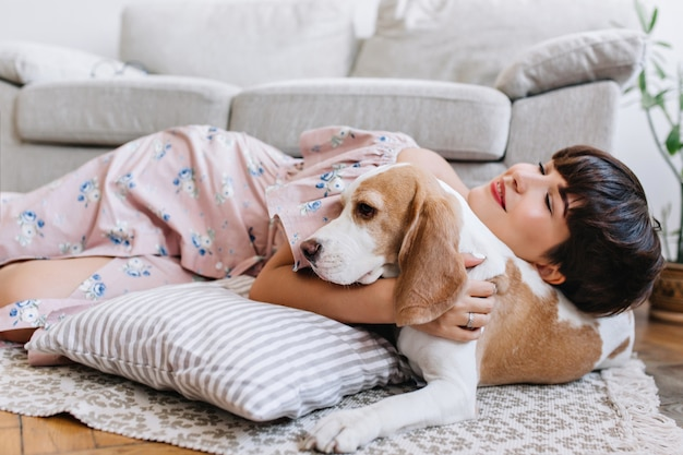Attractive girl with happy face expression lies on carpet near beagle dog with light-brown ears