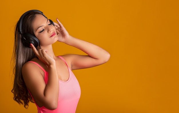 Attractive girl with headphones on a bright yellow wall. dj concept.