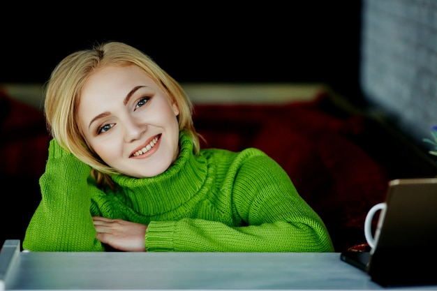 Attractive girl with light hair wearing green sweater sitting in cafe with tablet, freelance concept, online shopping, portrait.