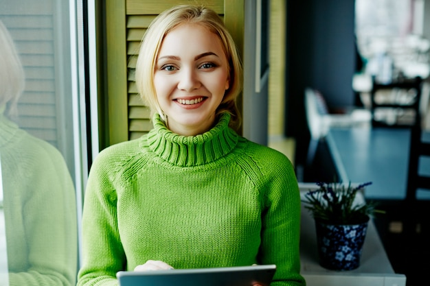 태블릿, 프리랜서 개념, 온라인 쇼핑, 초상화와 카페에 앉아 녹색 스웨터를 입고 가벼운 머리를 가진 매력적인 소녀.