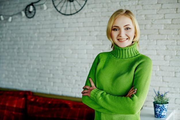 흰 벽 배경에 서 웃 고, 초상화 녹색 스웨터를 입고 가벼운 머리를 가진 매력적인 소녀.