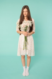 Привлекательная девушка с длинными волосами брюнетки в весеннем платье держит в руках белые цветы