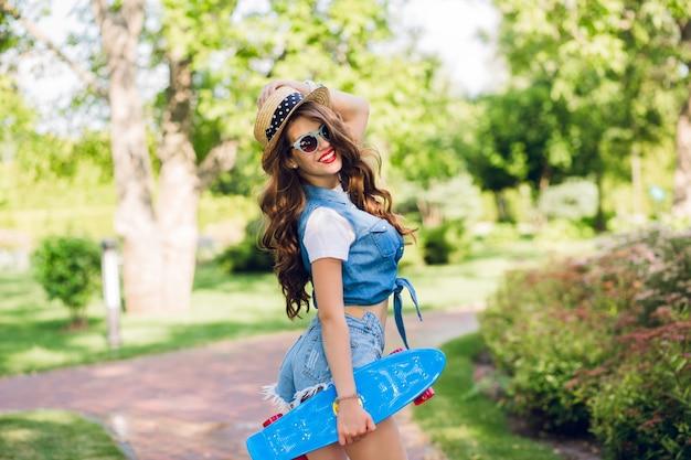 帽子とサングラスで長い巻き毛を持つ魅力的な女の子は、夏の公園でスケートボードでポーズをとっています。彼女はジーンズのジャーキン、ショートパンツを着ています。彼女はカメラに微笑んでいます。