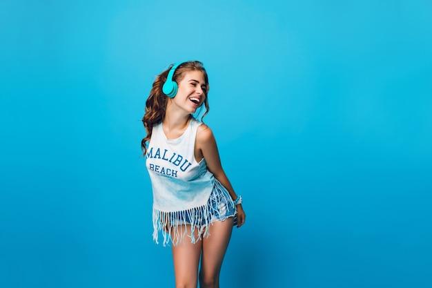 Attraente ragazza con lunghi capelli ricci in coda si diverte su sfondo blu in studio. indossa maglietta bianca, pantaloncini e ascolta musica energetica con le cuffie blu.