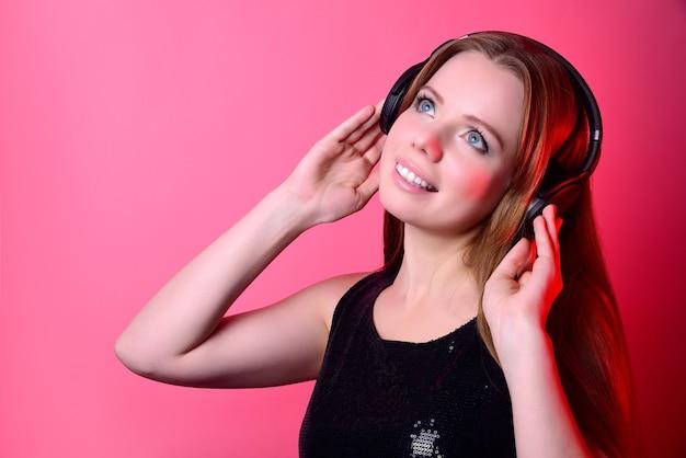 분홍색 배경에 음악을 듣고 대형 무선 헤드폰에 긴 머리를 가진 매력적인 소녀