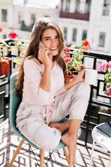 Attraente ragazza con i capelli lunghi in pigiama parlando al telefono sul balcone nella mattina di sole. tiene una tazza e sorride.