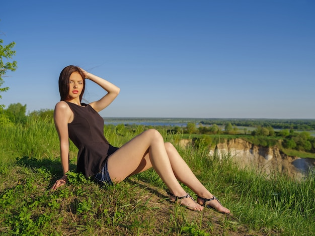 長い髪の魅力的な女の子は屋外でリラックスします。自然の屋外の崖のそばに座っている若い女性。晴れた夏の日にフィールドでポーズをとる女性モデル。