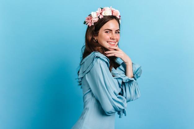いたずら好きな笑顔の魅力的な女の子がカメラを覗き込みます。花の冠を持つ青いドレスの女性の写真。