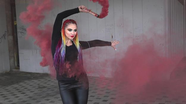 色とりどりの三つ編みと黒のドレスのメイクで魅力的な女の子。赤い人工煙の後ろに隠れてポーズをとる