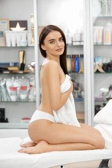 完璧な肌の美容院に座っている白いパンティーを身に着けている裸の背中を持つ魅力的な女の子