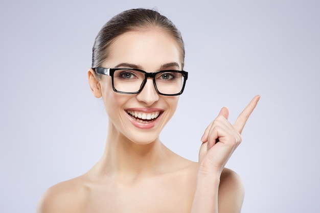 Attractive girl with nude make up posing at grey studio background, beauty photo concept, perfect skin, wearing glasses, vision concept, having an idea.