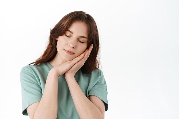 Привлекательная девушка с обнаженным натуральным макияжем, положив голову на руки и спящая, опираясь на ладони, имея сладкий сон, стоя у белой стены