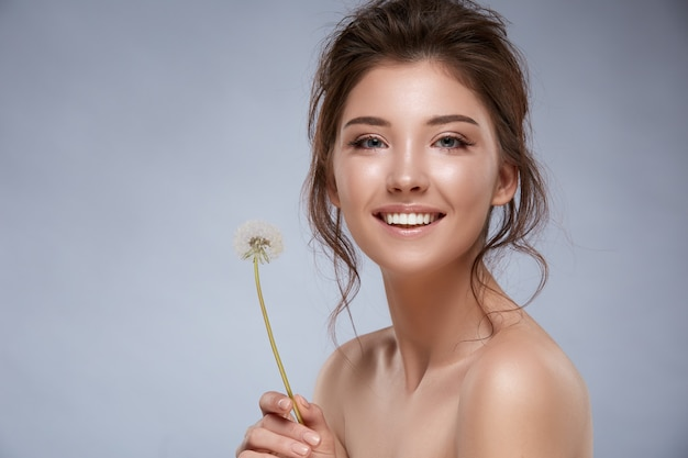 Привлекательная девушка с идеальной кожей и обнаженными плечами держит одуванчик и улыбается