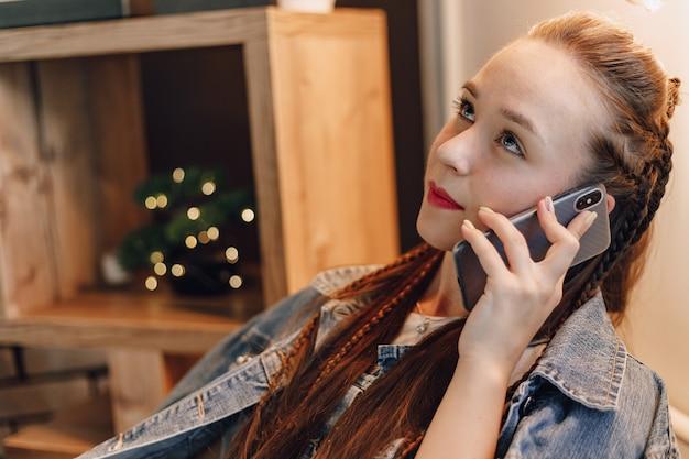 誰かと話している電話で魅力的な女の子。モバイルネットワークによる通信。