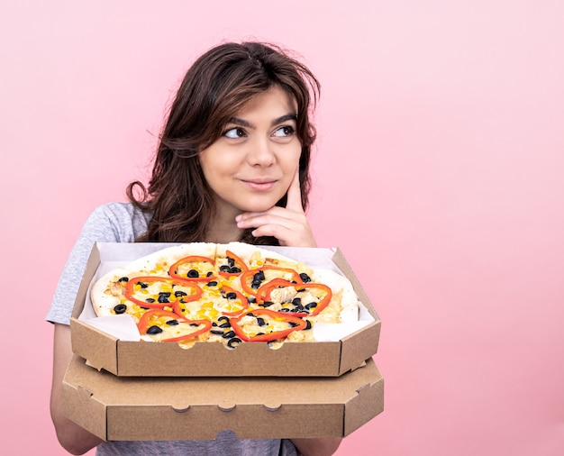Attractive girl with pizza in a box for delivery on a pink background