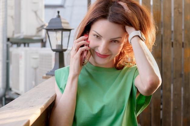 Привлекательная девушка с рыжими волосами в зеленой блузке разговаривает по мобильному телефону на открытой террасе кафе. деловая женщина ведет переговоры по телефону.