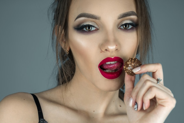 Attractive girl with red lips eats chocolate candy and looking at the camera in studio