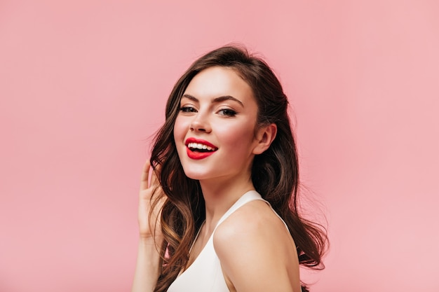 Attractive girl with red lipstick and curly dark hair looking at camera on pink background.