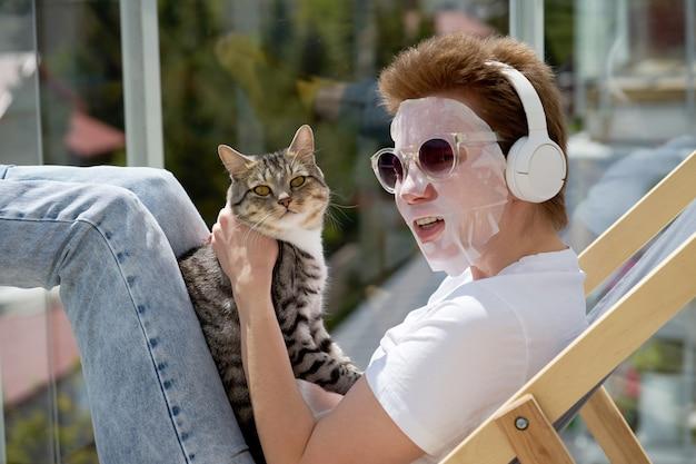 Привлекательная девушка с стильной прической, применяя маска для лица на лице, играя с кошкой и слушать музыку.