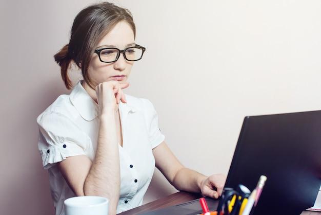 ノートパソコンで入力する眼鏡の魅力的な女の子