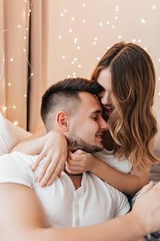 부드럽게 그녀의 남자 친구를 만지고 물결 모양의 머리를 가진 매력적인 소녀. 편안한 젊은 사람들의 실내 사진은 흰색 옷을 입습니다.