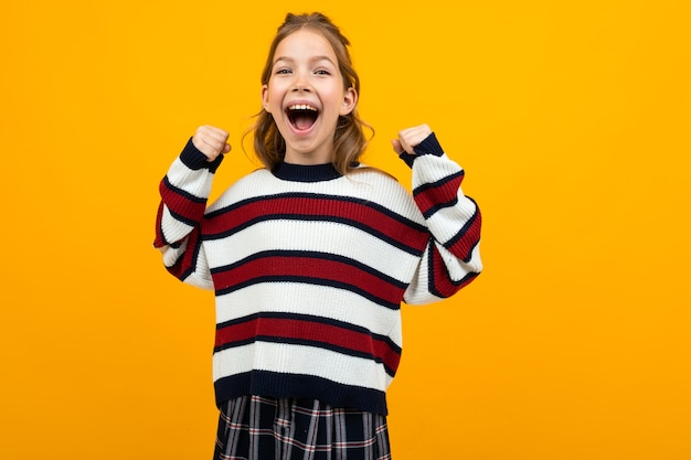 Attractive girl with wide open mouth shouting news on a yellow studio background with copy space.