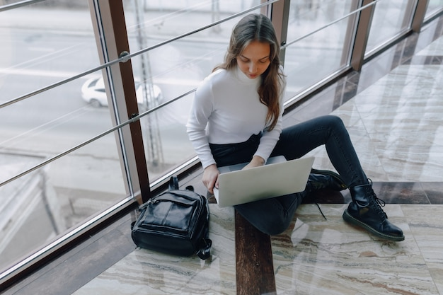 Attractive girl working with laptop and things in airport terminal or office on floor. travel atmosphere or alternative work atmosphere.