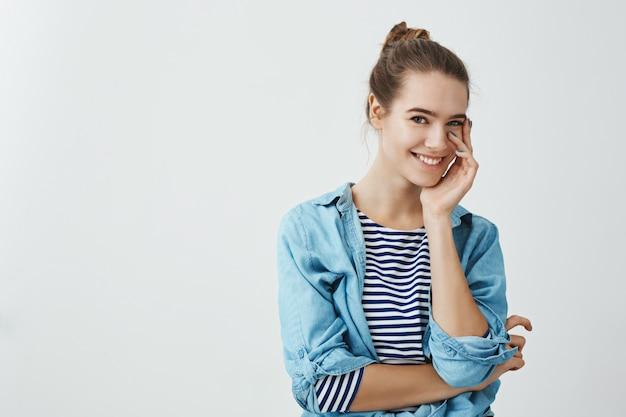 La ragazza attraente non può smettere di guardare il ragazzo. donna caucasica snella con la guancia tenera commovente dell'acconciatura del panino con la palma e sorridere allegramente mentre controllando parete grigia.