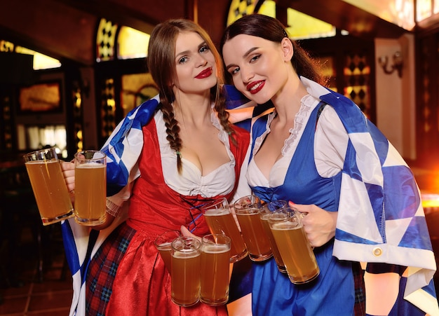 Attractive girls in bavarian clothes with the oktoberfest flag.