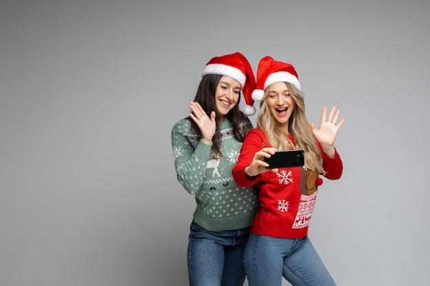 빨간색과 흰색 크리스마스 모자를 쓴 매력적인 여자 친구는 전화로 셀카를 합니다.