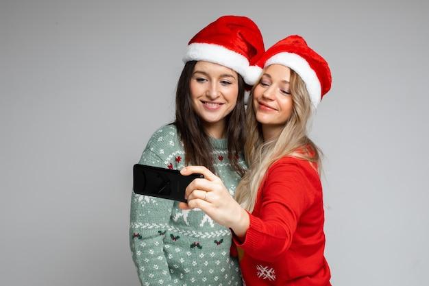 빨간색과 흰색 크리스마스 모자를 쓴 매력적인 여자 친구가 셀카를 위해 포즈를 취합니다.