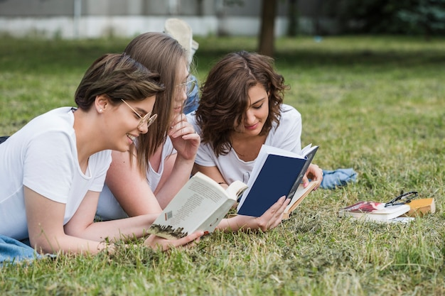 Attractive girls friends reading together in summer